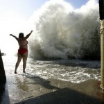A woman stands in front of a large wave